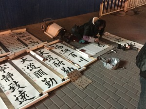 A woman painting large character posters for sale in the gloom